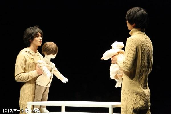 それぞれ人形を抱いて、小さな兄弟を演じる安西さん(左)と小林さん(右)