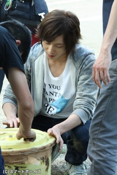 タイムカプセルのバケツに、職人技(?)で土を刷り込んでいく染谷さん