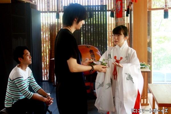 玉串奉奠の説明を聞き、榊を受け取る一慶さん
