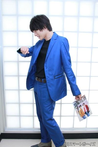 【パンフレットを使っての寸劇(?)ショット②】 スーツケースを引きながら時間を確認するモデルを演じている崎山さん