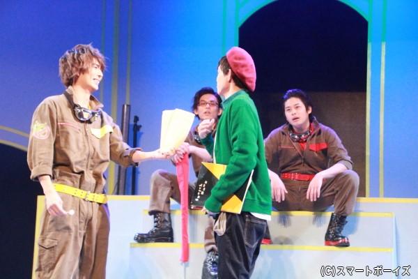 東将司さん演じる小澤徹(右から2人目)が「バグバスターズ」を取材するところから物語がスタート