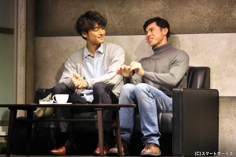 探偵・迫田 勝(右・小島よしおさん)の事務所を訪れた羽沼弘毅(左・内田裕也さん)は、殺人ビジネスの噂を語る