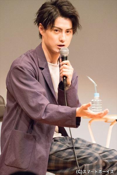 同じハンバーガーの持ち方をするお客さんへ話しかける松村さん