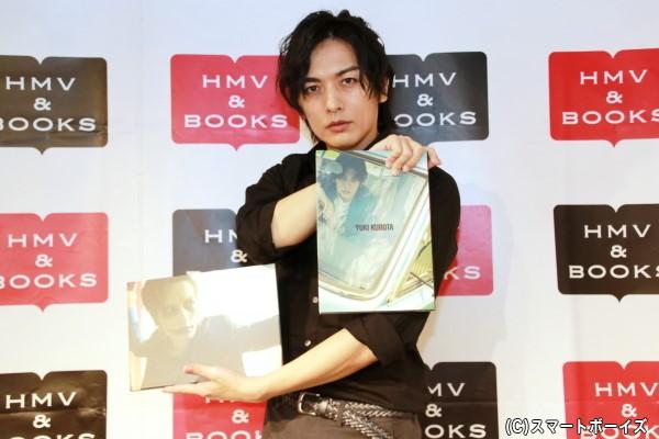 表紙がお気に入りカットという写真集(右)と道化師メイクが印象的なDVD(左)を持つ久保田さん