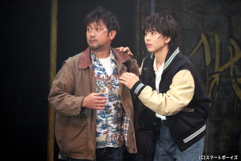 大学生の奥村英二(右・岡宮来夢さん)は、カメラマン・伊部俊一(左・冨田昌則さん)に同行しアッシュたちと出会う